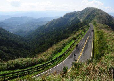 Horská silnička a cyklisté na severu ostrova Tchaj-wan