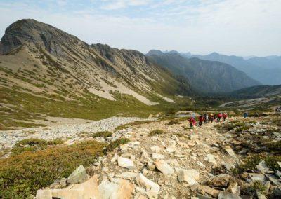 Skupina turistů pod vrcholem hory Xueshan a s výhledy na hřeben Holy Ridge