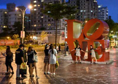 Turisté u nápisu Love před mrakodrapem Taipei 101